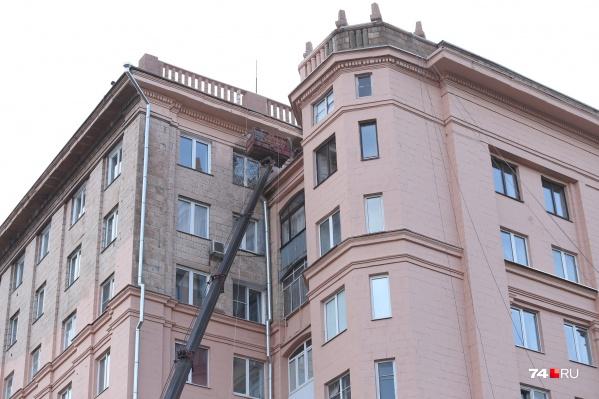 Рабочие закрасили исторический фасад с плитами дома на площади Революции, 1