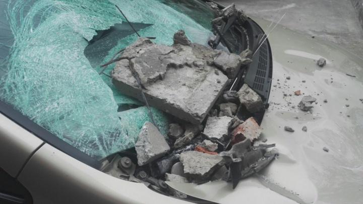 Кусок бетона с крыши дома расколотил иномарку