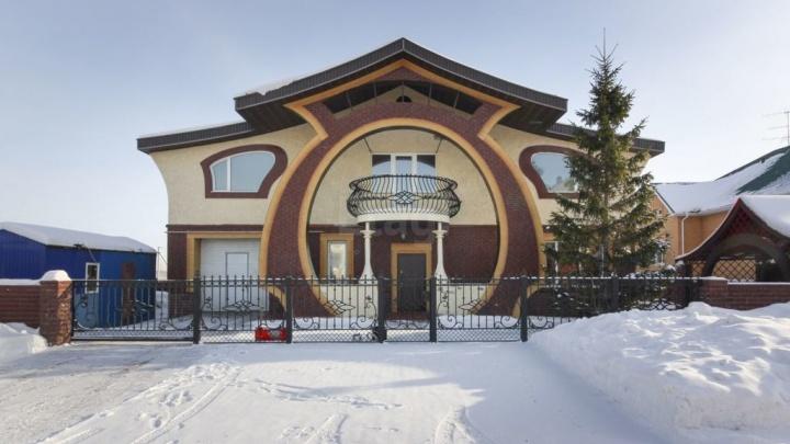 Омский строитель выставил на продажу коттедж с огромной аркой у входа и изогнутыми окнами