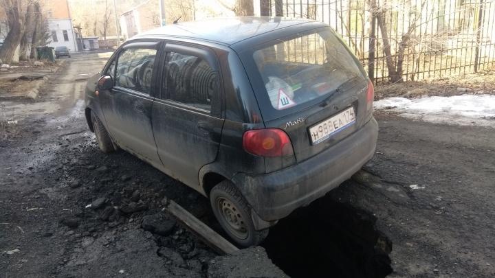 Провальный день: машина челябинки застряла в яме на дороге
