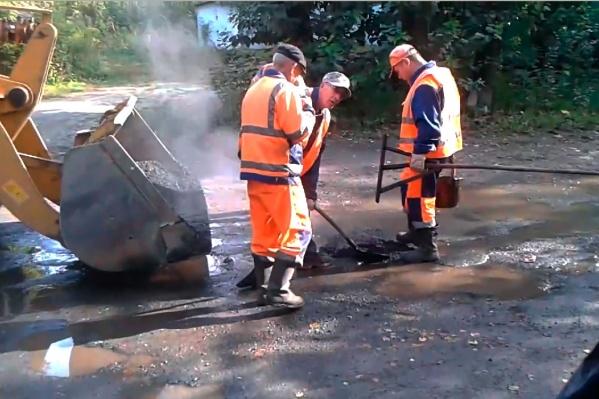 Рабочие засыпали асфальт в глубокую яму, наполненную водой