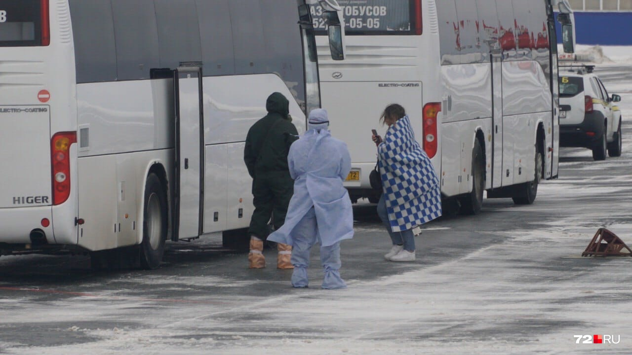 Пассажиры в одеялах заходят в автобусы. Всем им измерили температуру, теперь они отправляются в реабилитационный центр в посёлке Винзили
