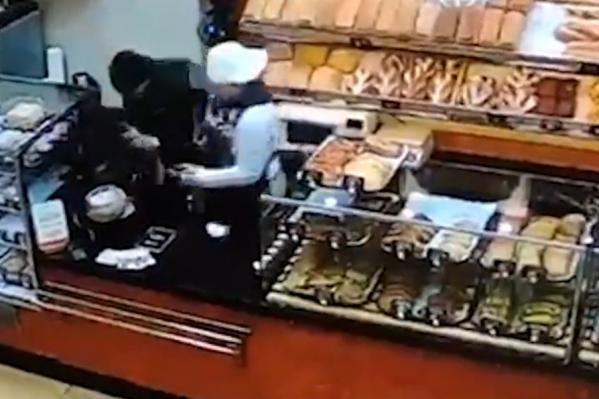 Женщина оттаскивала грабителя от кассы