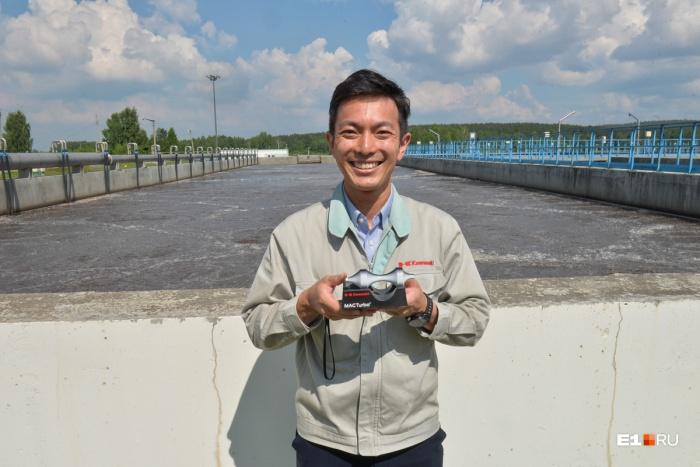 В руках у представителя Kawasaki — модель турбины, а за спиной — сточные воды Екатеринбурга