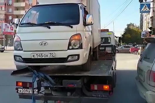 Видео: эвакуатор увёз из центра Новосибирска машину с водителем за рулём
