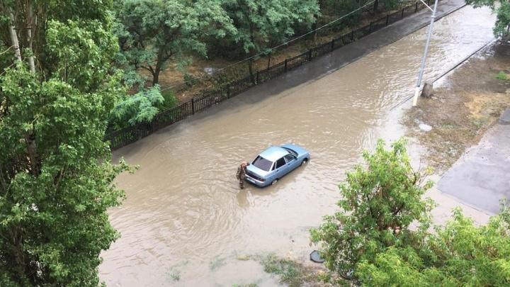 На дорогах Волгограда коммунальщики под толщей воды ищут ливневки