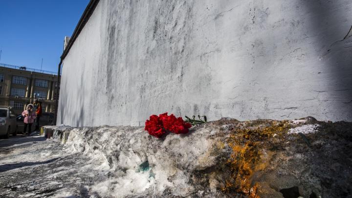 К стене, на которой закрасили популярные граффити, положили траурные цветы