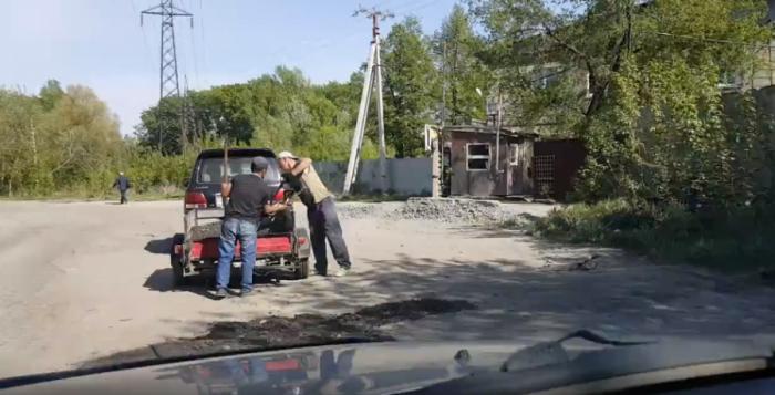 Кадр из видео, на котором добровольцы ремонтируют проезд