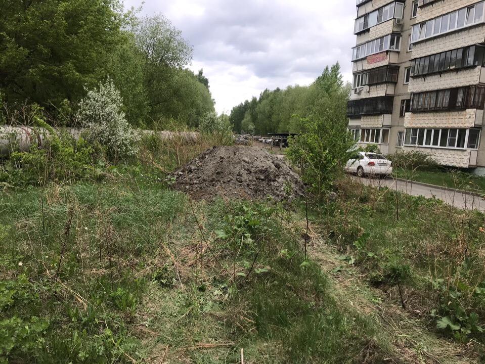 Кучи земли с кусками асфальта и щебня рабочие начали сгружать на газон, где жители высаживали кустарники и деревья