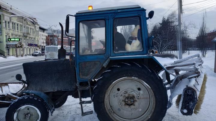 Тракторист с огромным плюшевым медведем в кабине очищает центр Омска от снега