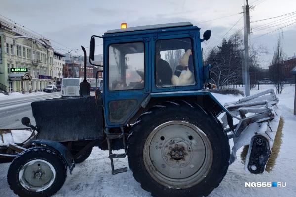 Медведь устроился у заднего стекла трактора