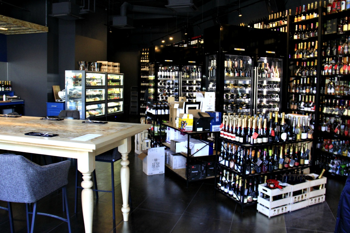 Бутылками в винотеке заняты до потолка все полки вдоль одной из стен и два винных холодильника