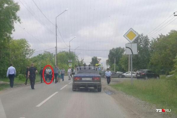 Подозреваемого ведут в наручниках в сопровождении полиции