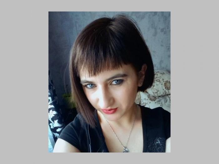 У девушки каштановые волосы и голубые глаза