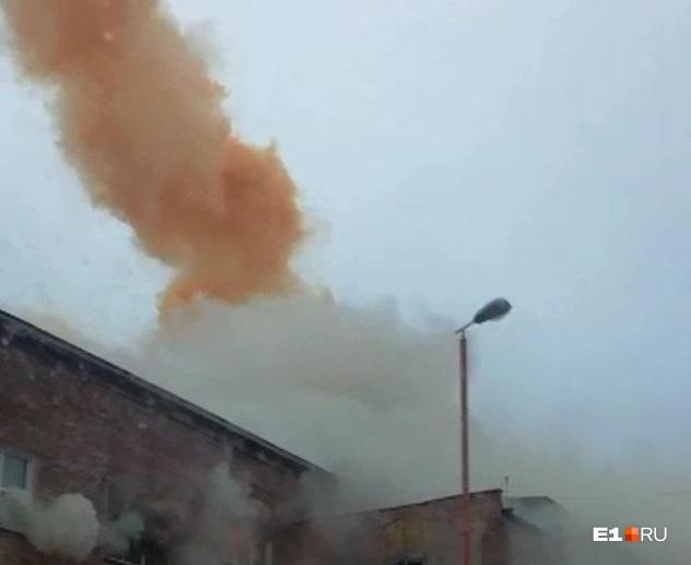 В воздухе оранжевый дым, а около здания завода — обычный серый
