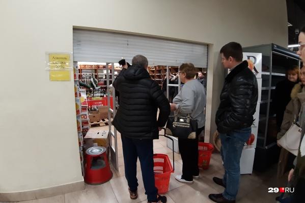 Покупателей пускают в винный по одному, чтобы они не разгромили полки, которые за два дня почти опустели