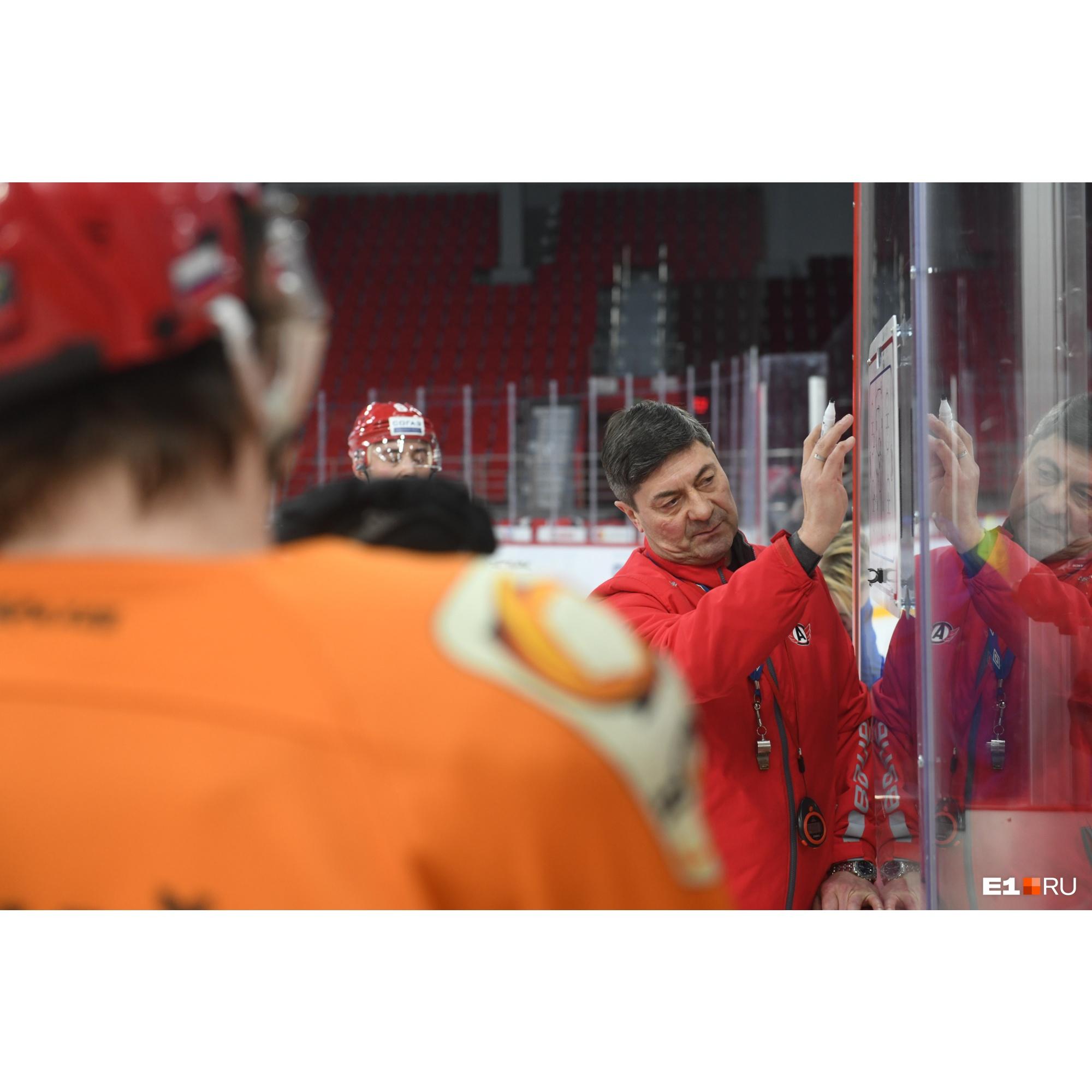 Главный тренер на планшете рисует, какие упражнения должны отработать хоккеисты