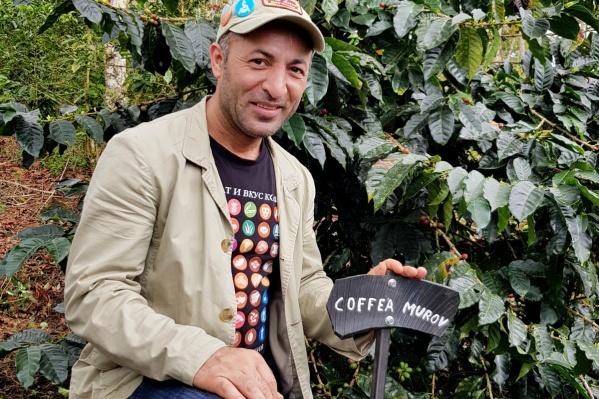 Муров Ахмедов у куста кофе со стандартной табличкой, на которой обозначен его сорт