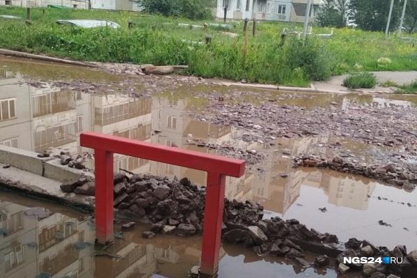 Разбитая дорога, яма и лужа у дома на Ястынской