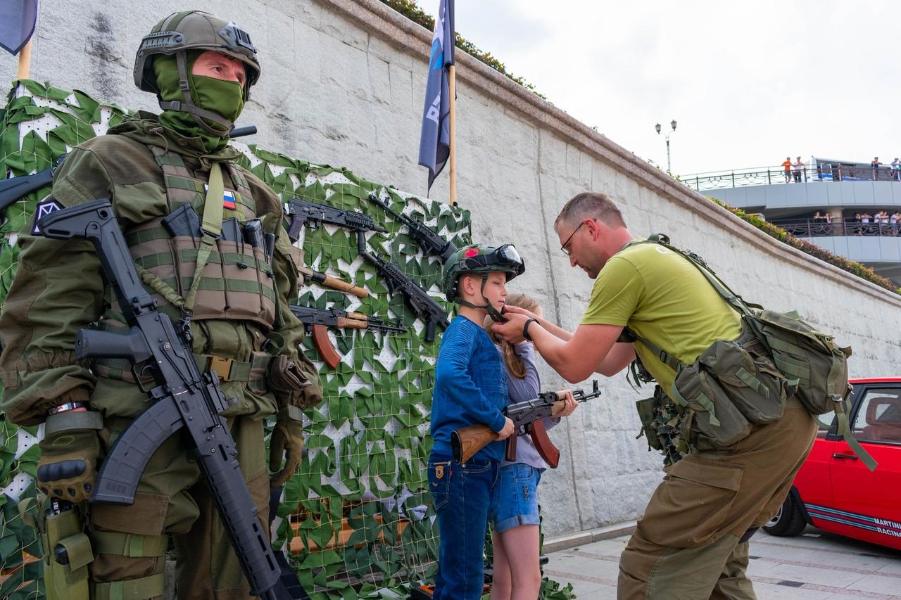 Ну, куда же без патриотического воспитания и демонстрации оружия. Вы, кстати, как относитесь к тому, что детям дают в руки оружие и примеряют на них военную форму?