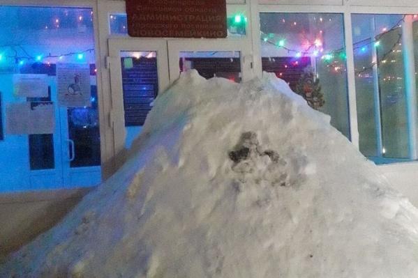 Огромная куча снега преградила вход в здание администрации