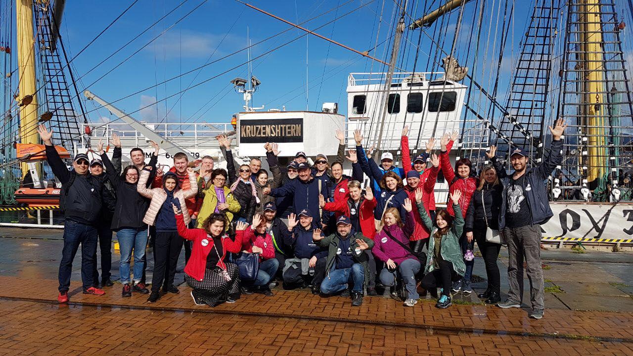 Вся большая команда туристов на фоне парусника