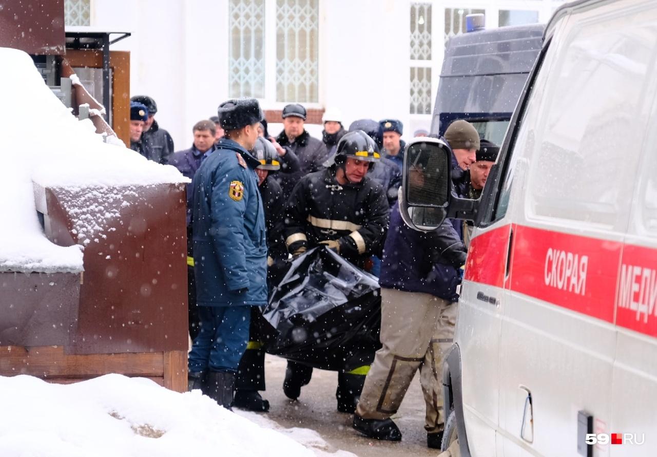 Спасатели помещают погибших в машины скорой помощи