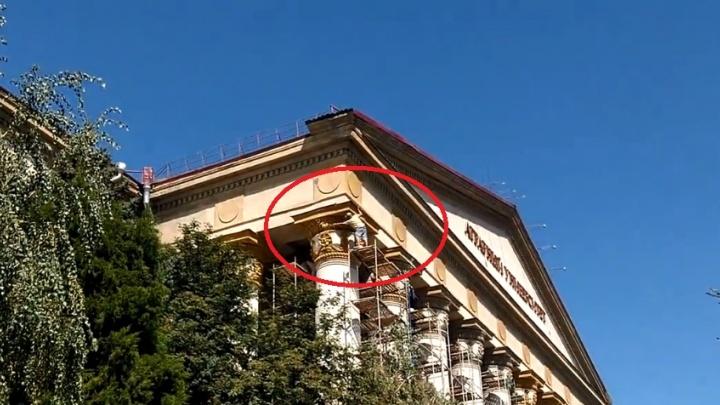 Под контролем: в Волгограде рабочие без страховки красят на высоте колонны аграрного университета