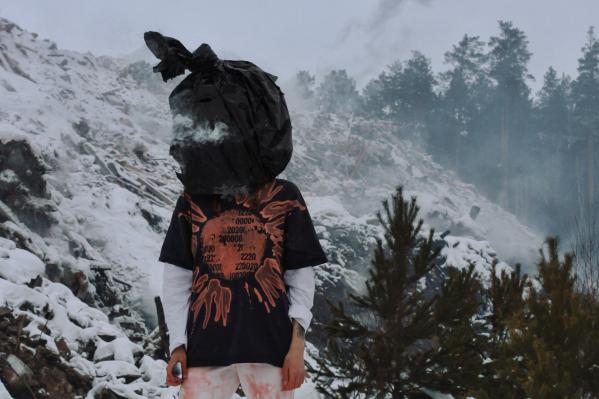 Девушка с дымящимся пакетом на голове позировала на фоне горящей свалки