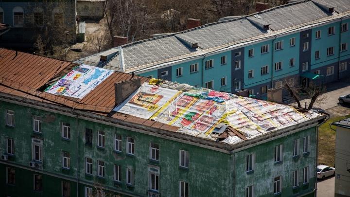 Крышу пятиэтажки на Котовского накрыли баннерами с рекламой шпикачек и кофе