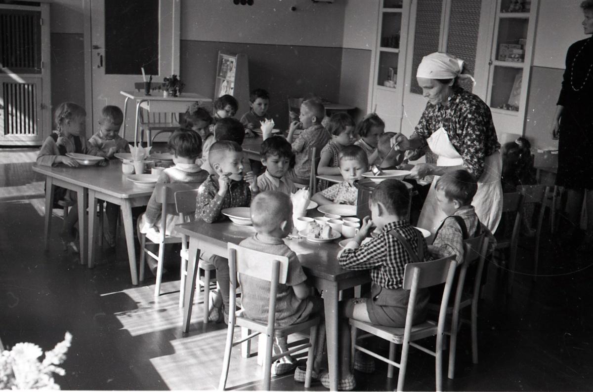 Обед в советском детском саду, на столе рядом с детьми —большая кастрюля с горячим супом. Сейчас это бы сочли нарушением техники безопасности