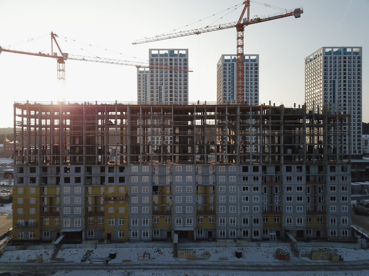 На семи этажах уже выложили наружные стены из блоков, а на первых —остеклили окна и начали работы по теплоизоляции и шумоизоляции стен