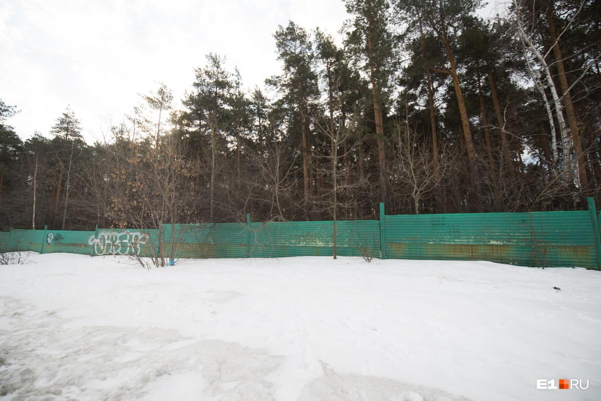 Кладбище прячется за зеленым забором