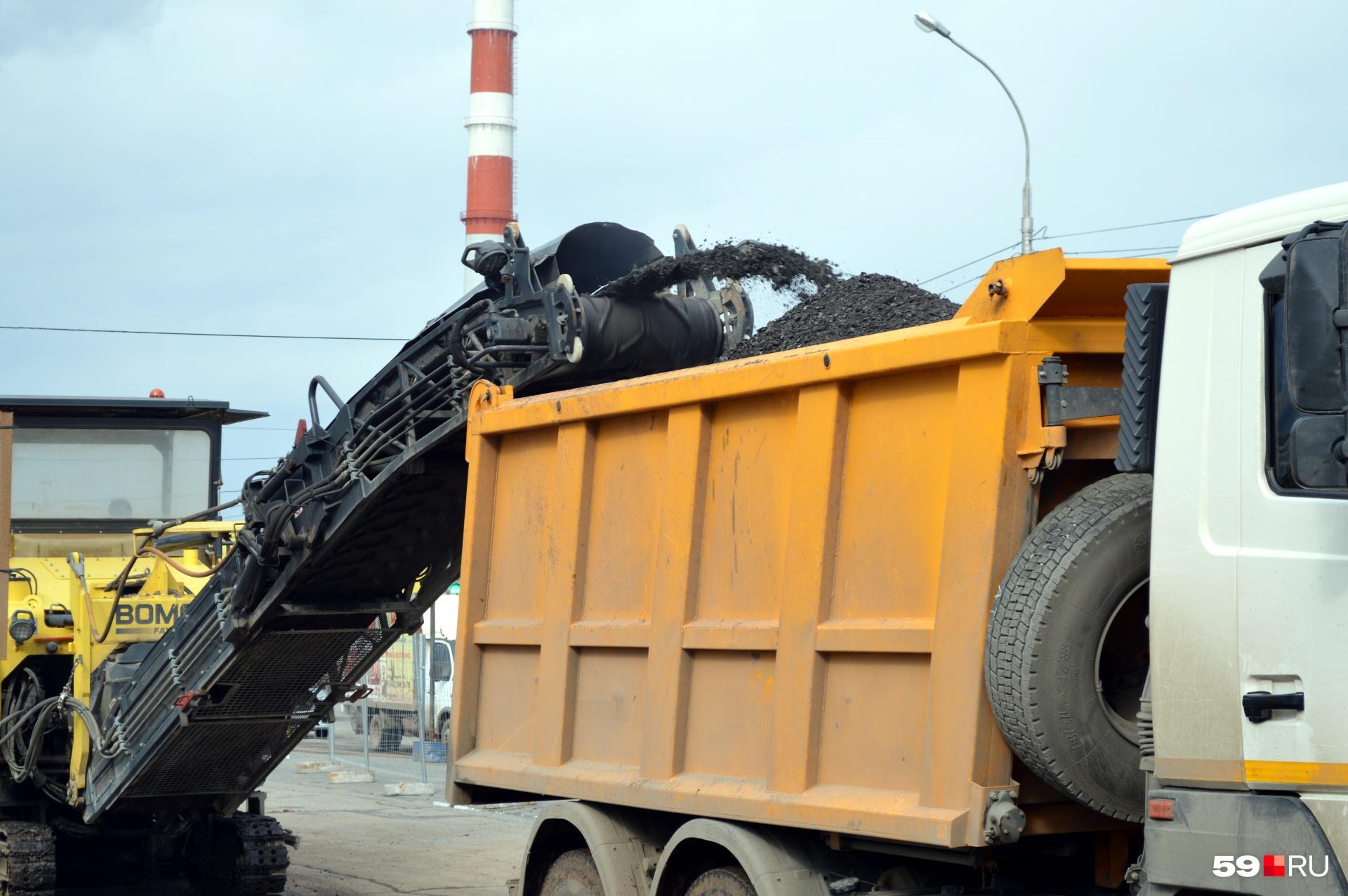 Измельченный асфальт собирают в грузовики