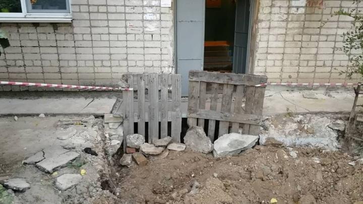 Экскаватор сломался: в Волгограде глубокую коммунальную яму прикрыли старой дверью