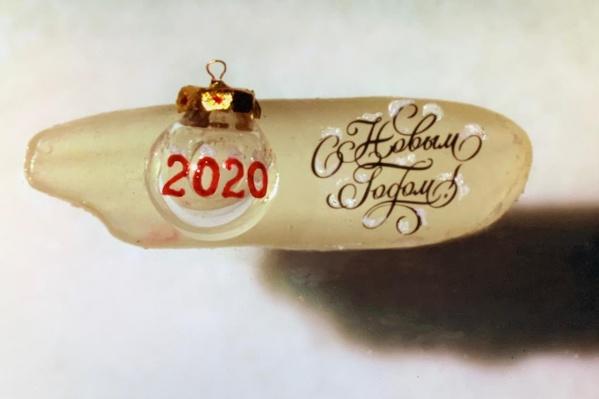 Помимо цифр на самой игрушке, миниатюрист написал на рисовом зёрнышке поздравление с Новым годом