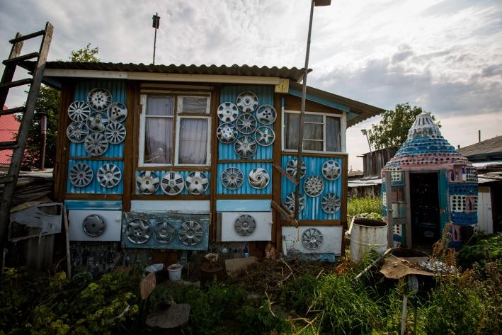 С другой стороны дома стены декорированы автомобильными колпаками