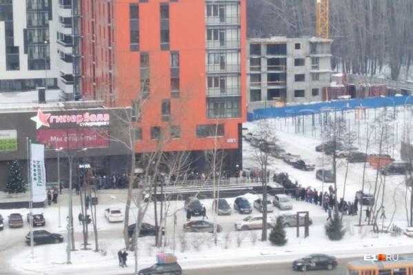 Люди выстроились в очередь к супермаркету