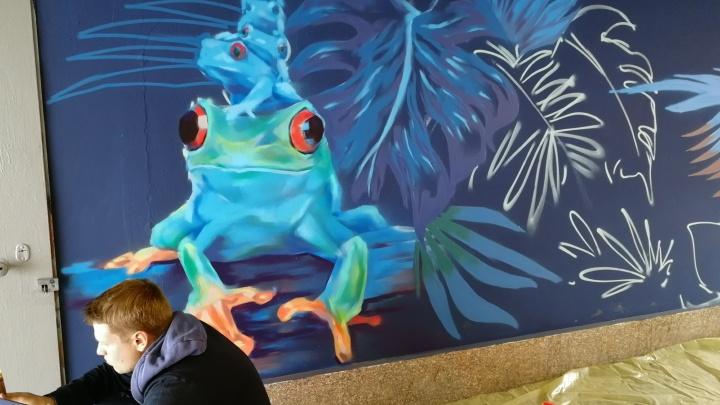 В переходе на «Туриста» рисуют зимний сад с игуанами, попугаями и лягушками: смотрим в прямом эфире
