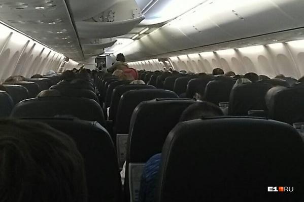 Пассажиры ждут, когда к самолёту приедет трап