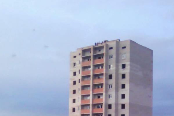 Дети сидят на самом краю многоэтажки
