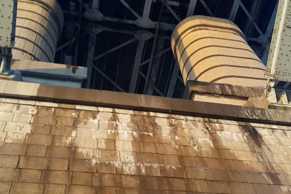 Опора моста стала мокрой от воды, которая льётся сверху