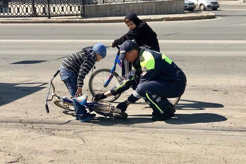 Полицейский просто починил мальчикам велосипед — в этот момент его и сфотографировали
