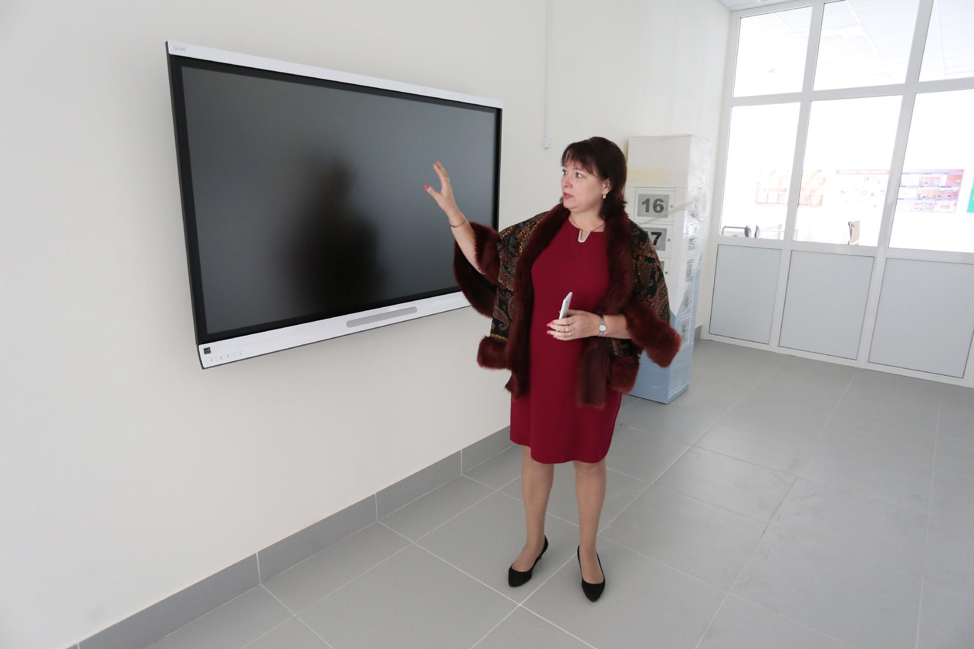 Директор школы Светлана Сергеева показывает в холле экран стоимостью около 400 тысяч рублей