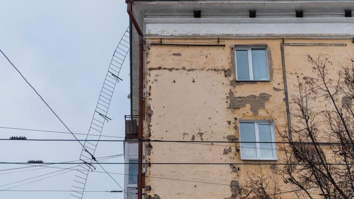 С крыши дома на Комсомольском проспекте свисают металлические перила