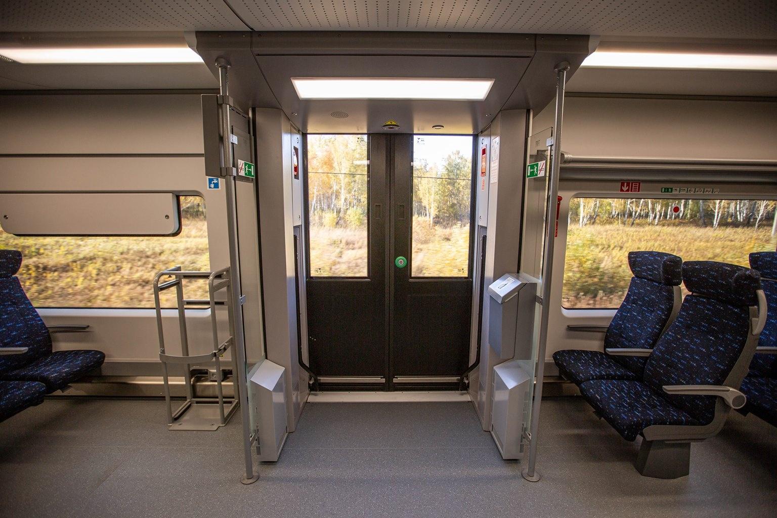Вход в вагон напоминает вход в обычный автобус. Зимой, по словам экспертов, чтобы пассажиры не мёрзли на стоянках, при открывании дверей будут включать несколько мощных кондиционеров. У входа поставили небольшие урны