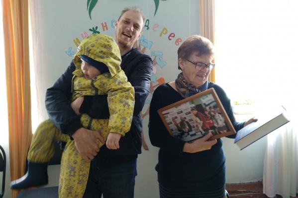 Сергей Ухов и его сын Глеб передали директору библиотеки книгу и фотографию со встречи с Джорджем Мартином