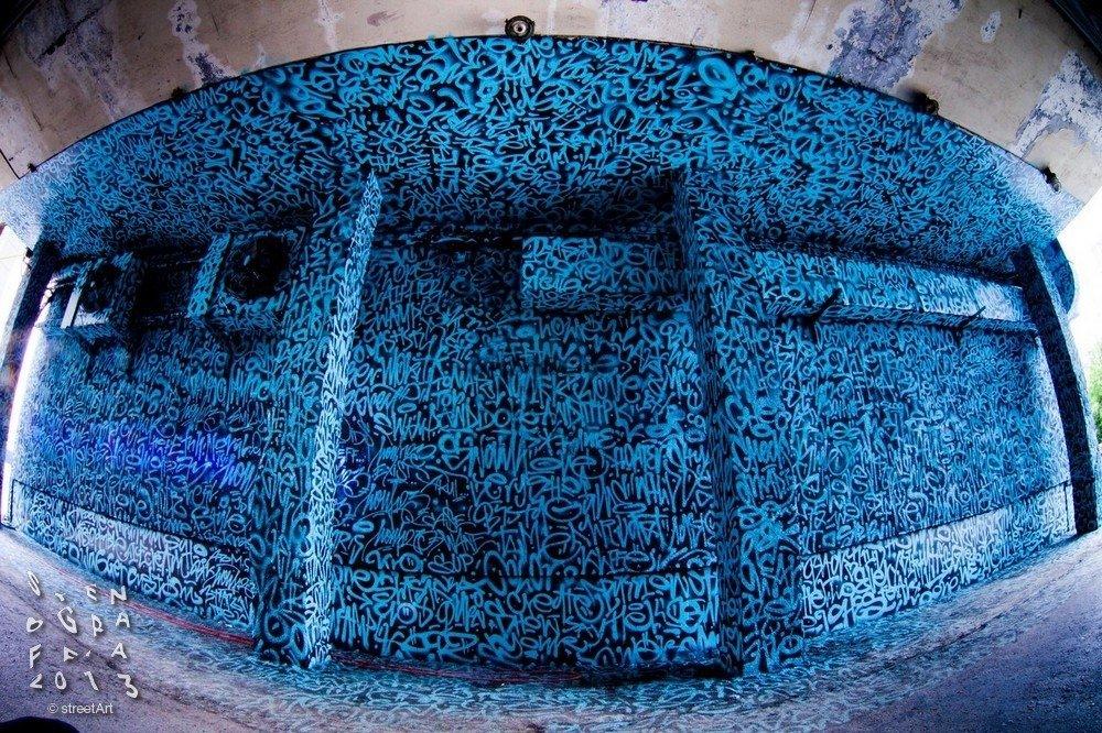 Эту работу у «Салюта» Покрас Лампас сделал в 2013 году.Ковёр из надписей — это не просто каракули или теги, а имена талантливых уличных художников. Под ультрафиолетом на стене проступает надпись All your walls are belong 2 us — «Все ваши стены принадлежат нам»