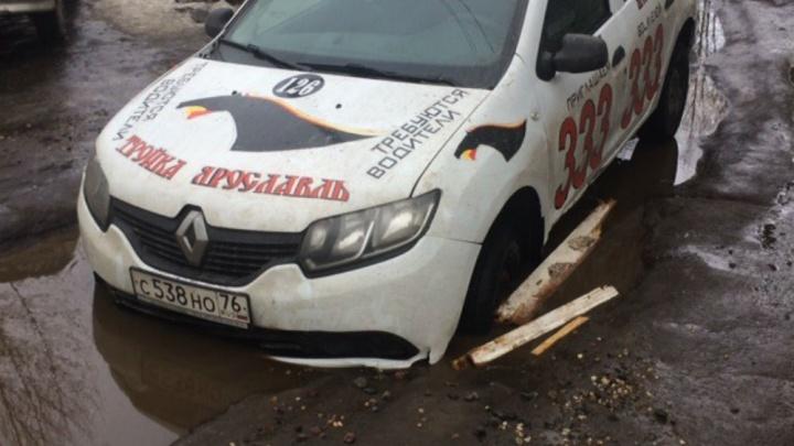 В Брагино в гигантской луже застряла машина популярного такси: видео