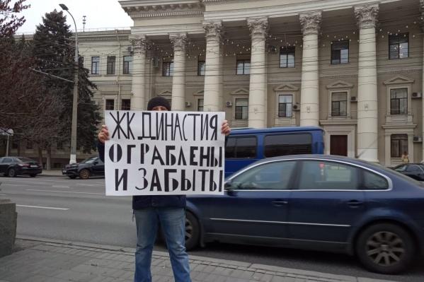 Дольщики по очереди выходят с плакатом под окна чиновников